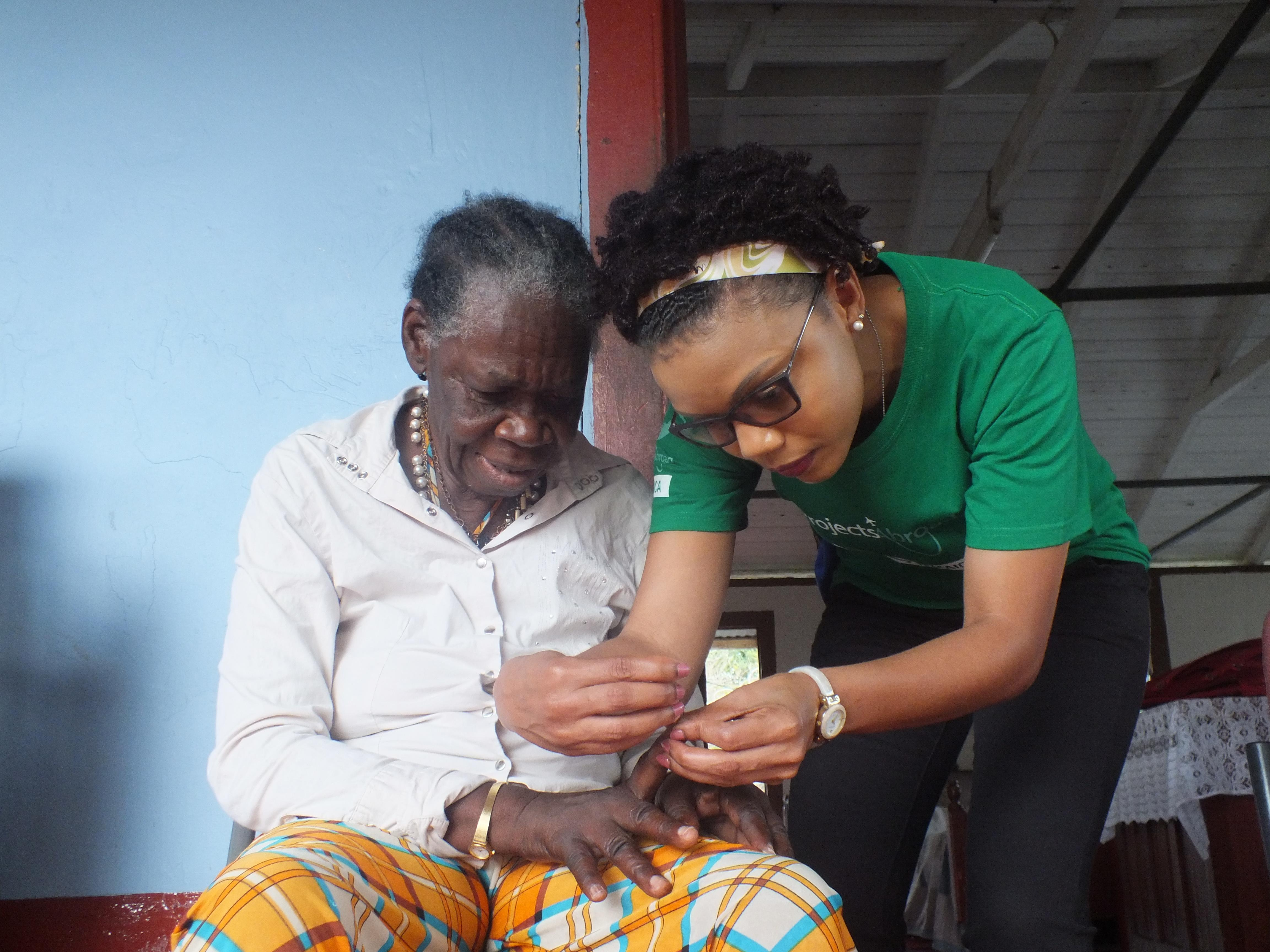 Projects Abroad volunteer helps an elderly woman with personal care during an outreach in Jamaica.